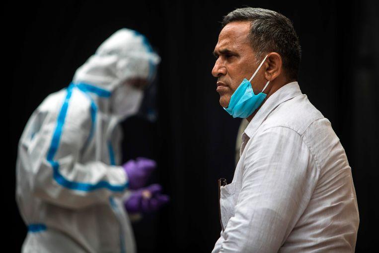 Een man wacht om getest te worden op het coronavirus in New Delhi, India. Beeld AFP