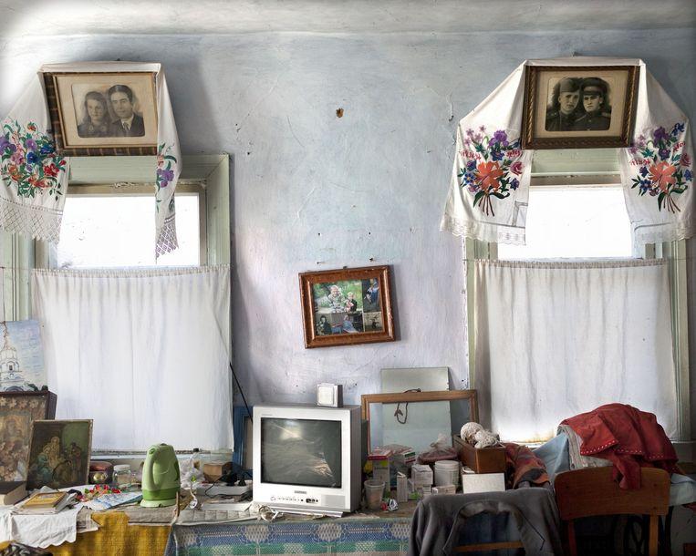 De slaapkamer van Maria Urupa (78). Overal in huis hangen foto's van familie. Haar man, een van de liquidators (schoonmakers van de centrale na de ramp), is 3 jaar geleden overleden. Maria woont in Pyrashiv Village samen met haar hondje. Beeld Esther Hessing