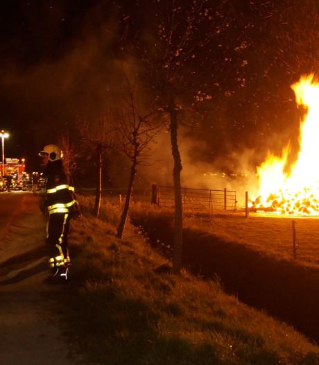Grote stapel boomstammen in brand in Wijk en Aalburg