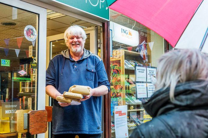 Eric Herni (61) in de deuropening van zijn boekenwinkel The Readshop met online bestellingen.