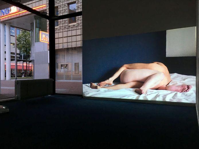 Het beeld komt uit de video-installatie waarin twee in elkaar verstrengelde mannen te zien zijn.