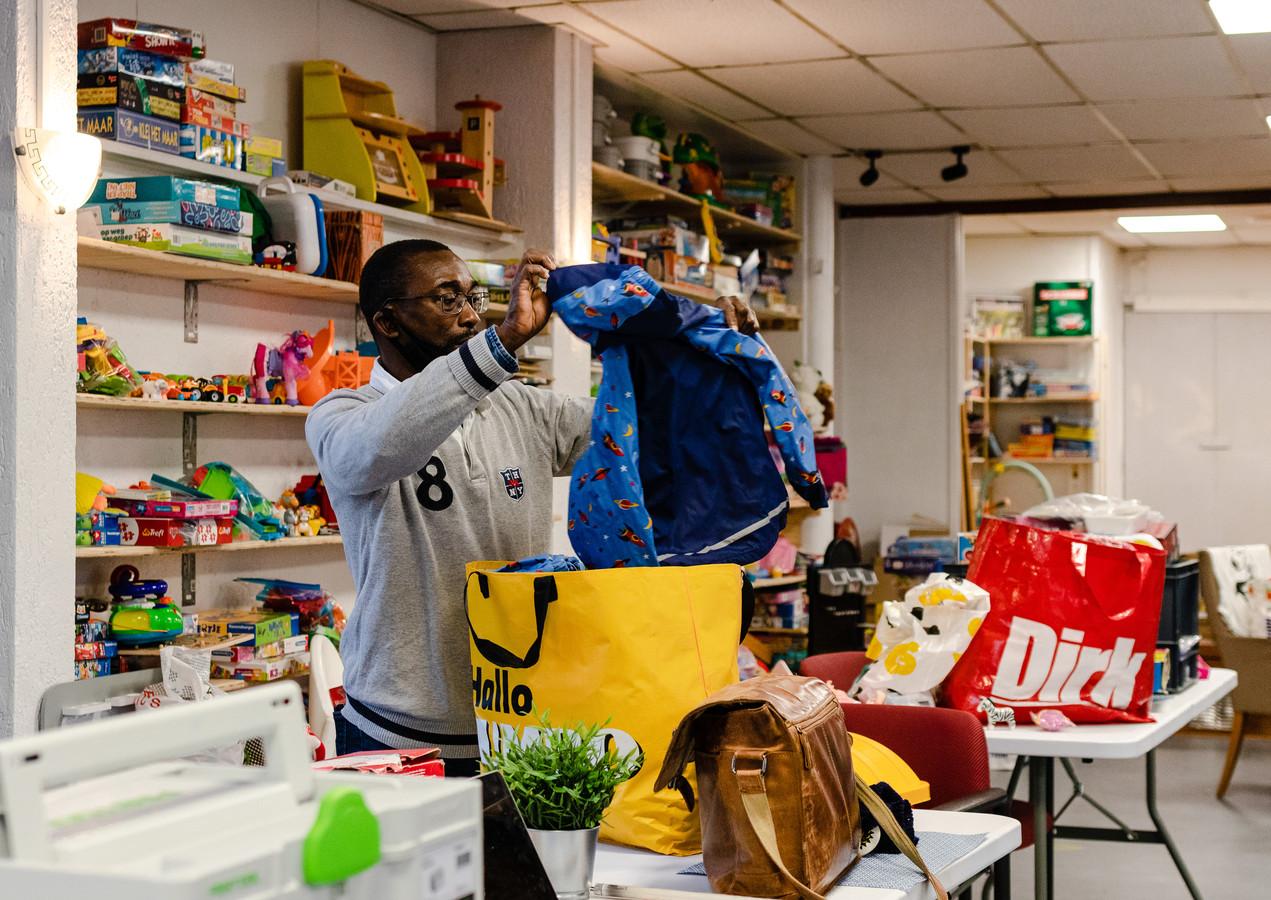 Vrijwilliger Frits Vrede (50) zoekt een tas uit die gedoneerd is aan Speelotheek Pip & Zo in Dordrecht. Gedoneerde kleding wordt naar de kledingbank gebracht.