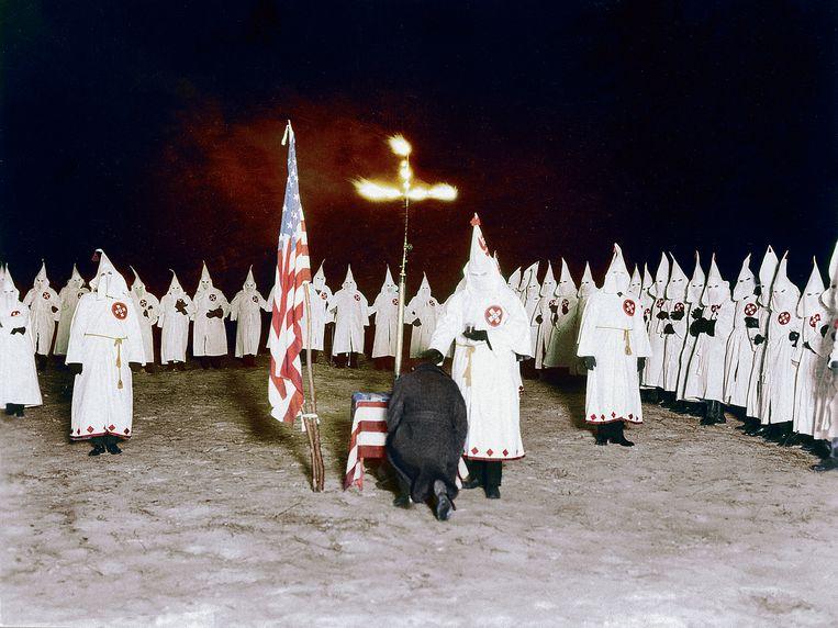 Een man knielt neer tijdens een initiatieceremonie van de Ku Klux Klan, jaren 20. Beeld RV Foto uit De tijd in kleur, uitg. Omniboek.