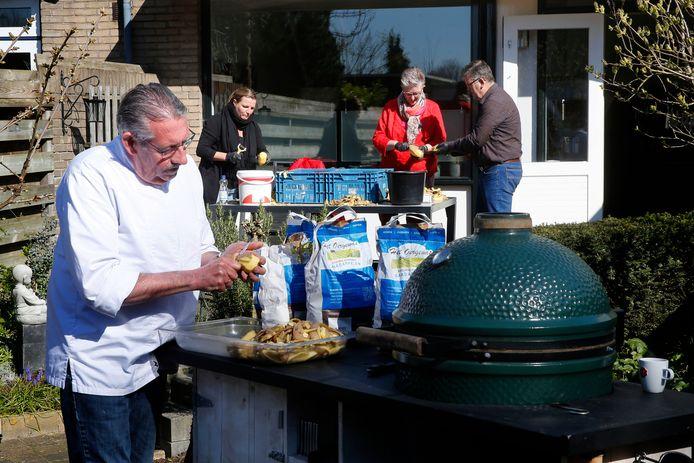 Chef-kok René Bakker schilt in zijn tuin aardappelen voor de puree die hij maakt. Zijn schilploeg is verderop aan het werk.