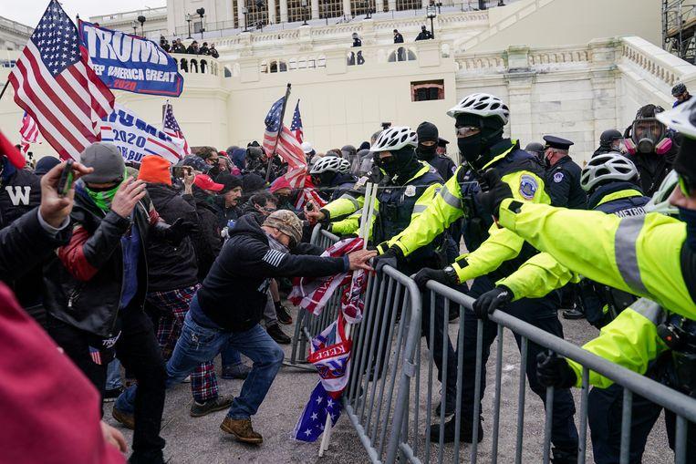 Fans van president Trump proberen een politiecordon te doorbreken. Beeld AP