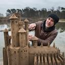 De italiaanse zandkunstenaar leonardo ugolini bezig met een zandkasteel dat hij maakt bij vormalig natuurbad Surae.