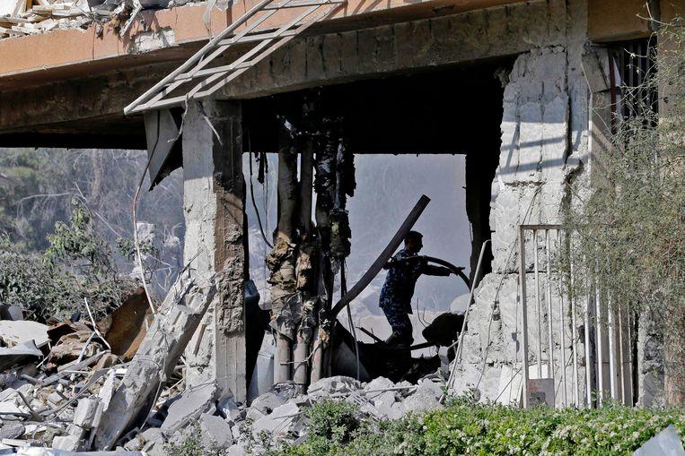 Syrische soldaten inspecteren de ruïnes van een van de getroffen gebouwen. Beeld AFP