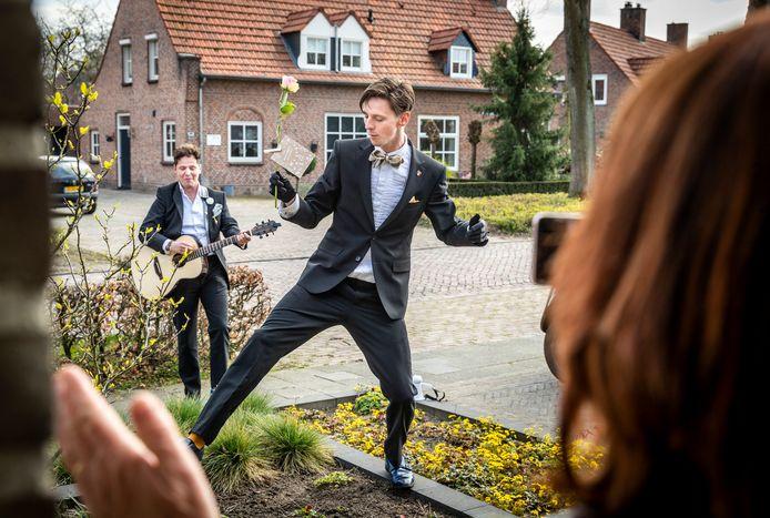 Jules Keeris (Graziano, met gitaar) en Peter Boven (Massimo) geven een serenade bij de voordeur van Rob en Anja Vriens, die toekijken met hun dochter Eefje.