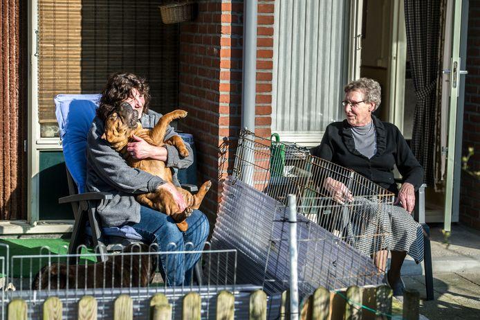 Bewoners zitten in de zon op hun terras. Op anderhalve meter afstand.