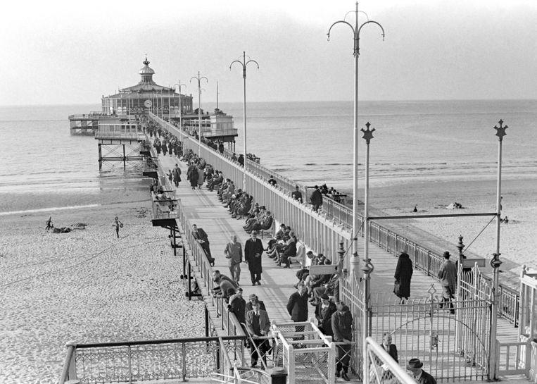 Op de eerste lentedag in 1936 gaan bezoekers de wandelpier op in Scheveningen. Later werd de pier iets noordelijker herbouwd. Beeld ANP