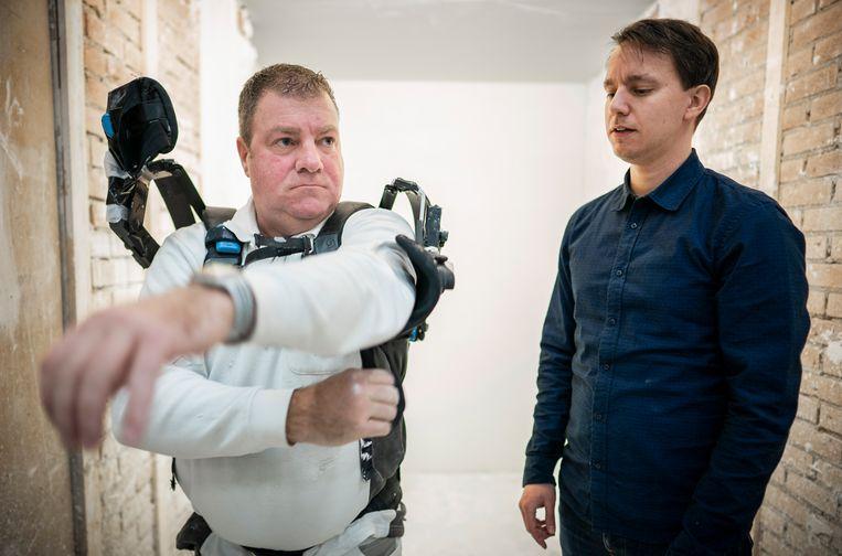 Een stukadoor trekt zijn exoskelet uit in een testomgeving in Veenendaal. Beeld Freek van den Bergh