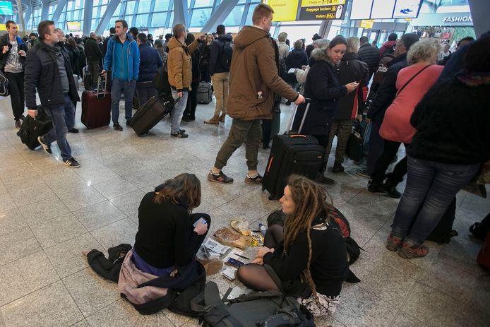 Gestrande reizigers op Eindhoven Airport nadat het vliegverkeer op 16 december stil werd gelegd vanwege de mist.