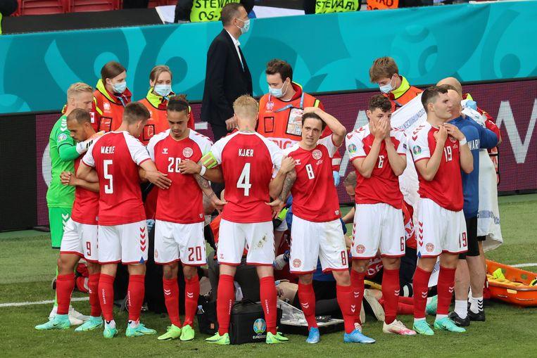 Spelers van het Deense elftal staan om Eriksen heen om hem aan het zicht van de camera's te onttrekken.  Beeld AP