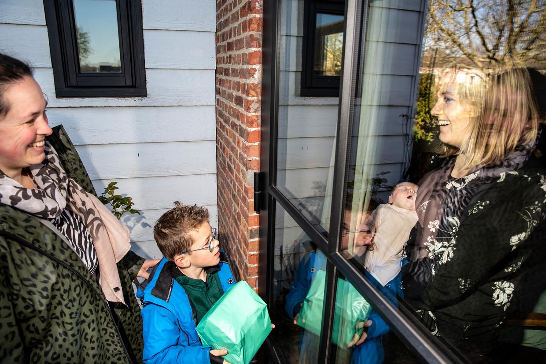 Moeder Kelly van Opdurp en dochter Liz mogen vanwege het coronavirus geen kraambezoek binnen ontvangen. Dus bewonderen vriendin Mariska de Ruijsscher en haar zoon Stan de baby vanachter het glas.