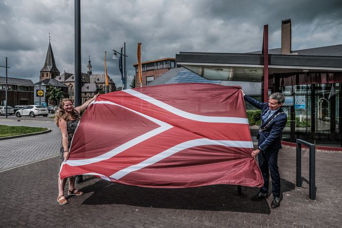De nieuwe Liemerse vlag, met de ontwerpster Sanne uit Groessen (links) en burgemeester Huub Hieltjes.
