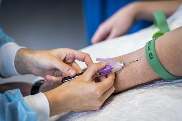 Een medewerker van de GGD in Limburg prikt bloed bij een deelnemer om te testen op antistoffen tegen het coronavirus.