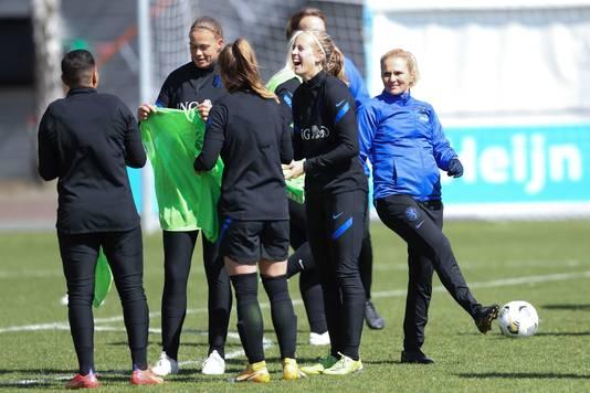 Sarina Wiegman ziet vanaf een afstandje hoe de speelsters op de training de grootste lol hebben.