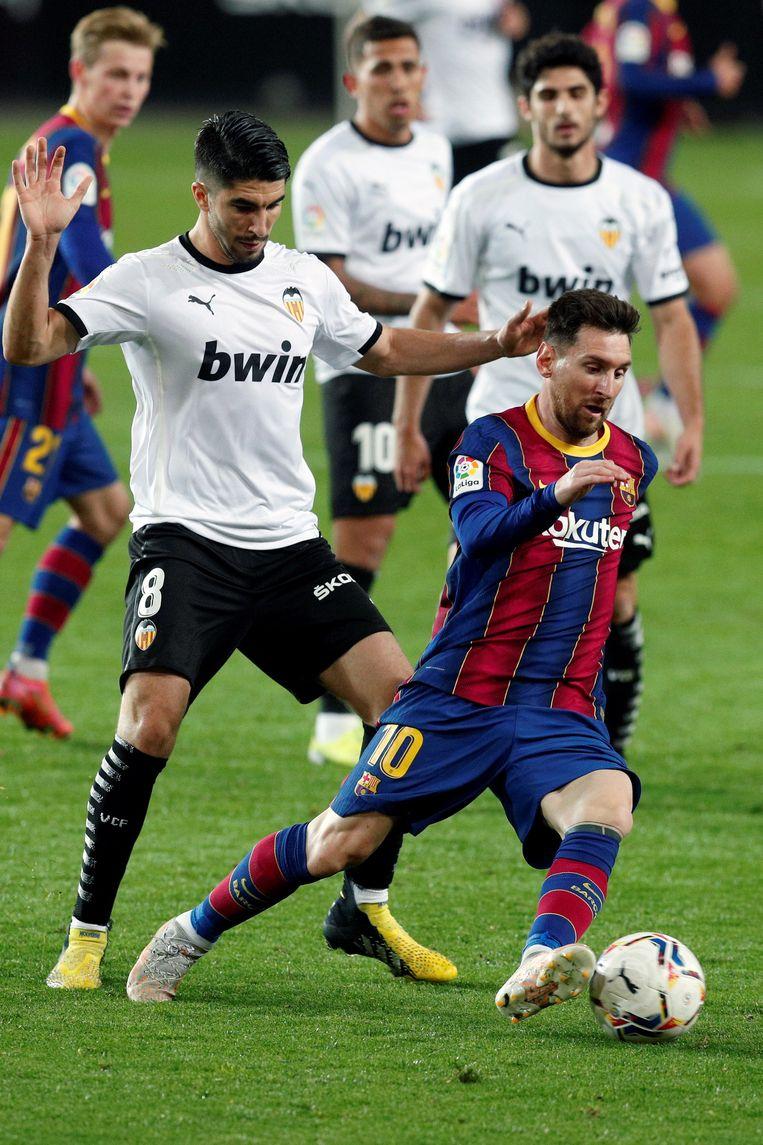 Messi passeert Carlos Soler (links) op 2 mei 2021 in de uitwedstrijd tegen Valencia.  Beeld EPA