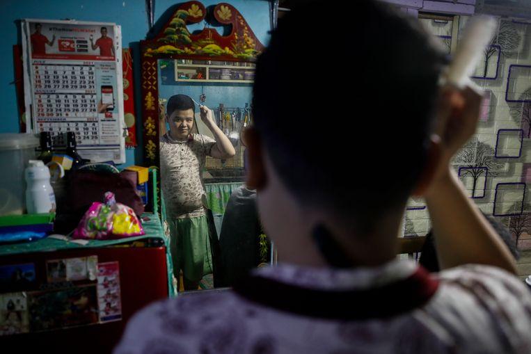 De dertienjarige Kurt Dave Justiniani ziet er straks piekfijn uit voor de eerste schooldag van het nieuwe jaar, die hij thuis in Quezon City zal meemaken. Vanwege de opleving van corona in de Filipijnen zullen miljoenen kinderen in dit land de komende tijd thuisonderwijs volgen.  Beeld EPA