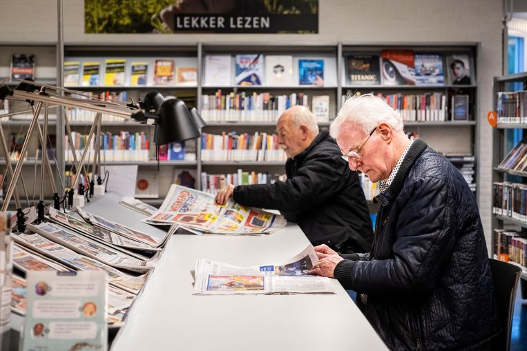 Twee gepensioneerde mannen lezen de krant in een bibliotheek. Beeld Hollandse Hoogte / Ramon van Flymen