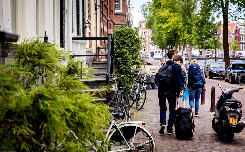 Toeristen met rolkoffer in Amsterdam.