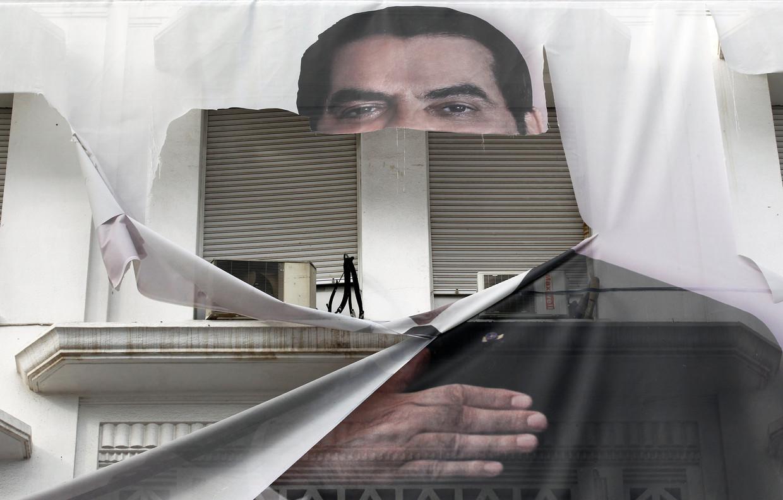 Een gescheurd spandoek van Zine El Abidine Ben Ali, voormalig president van Tunesië.
