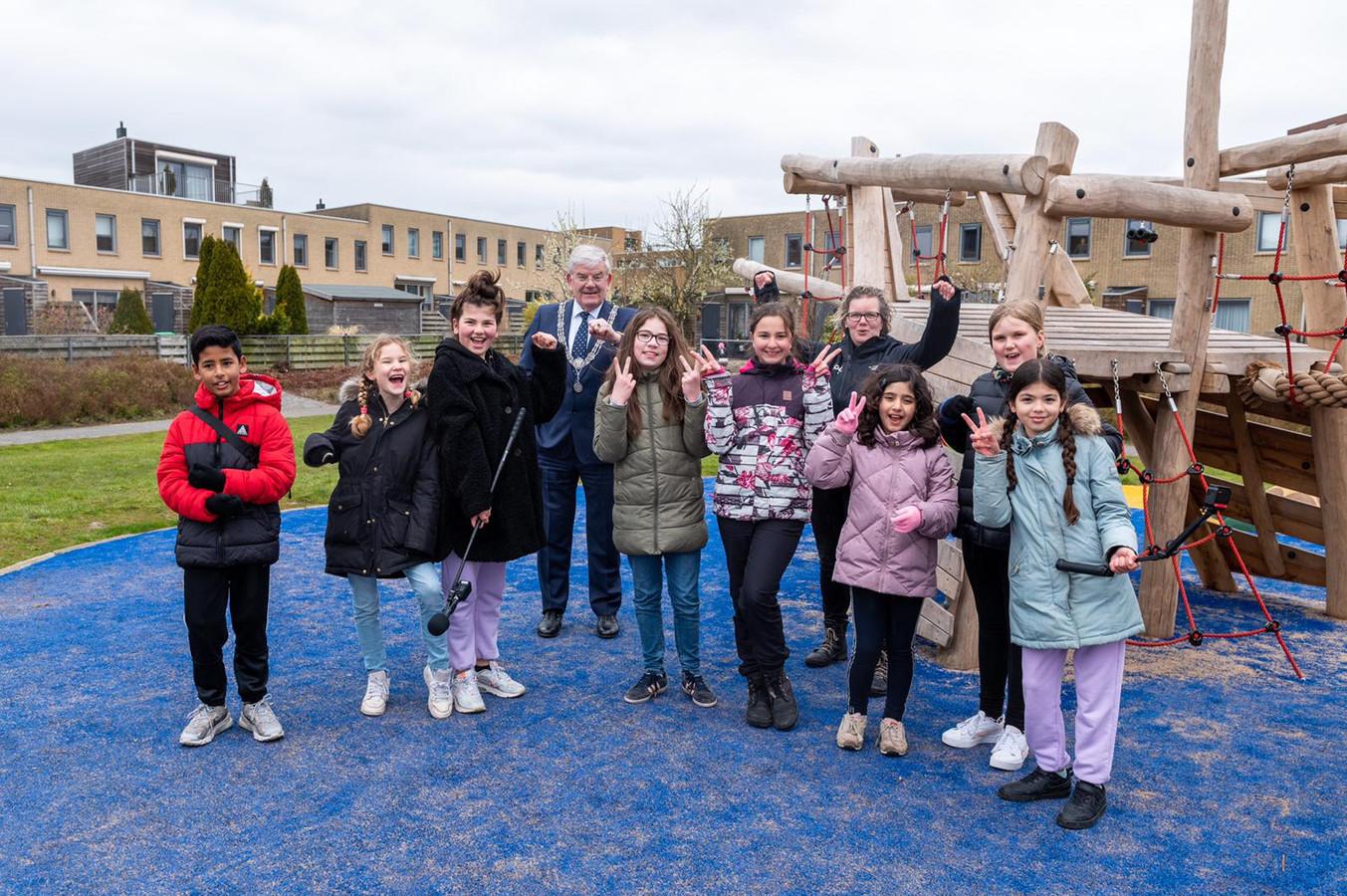 De kinderen van de Glazenmakerhof in Leidschenveen helpen burgemeester Jan van Zanen bij de opening van hun nieuwe speeltuin die ze zelf hebben helpen bedenken.