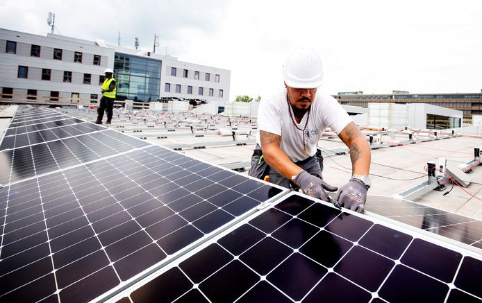 Mannen bezig met het installeren van zonnepanelen op het dak van de TU Delft. Foto ter illustratie.