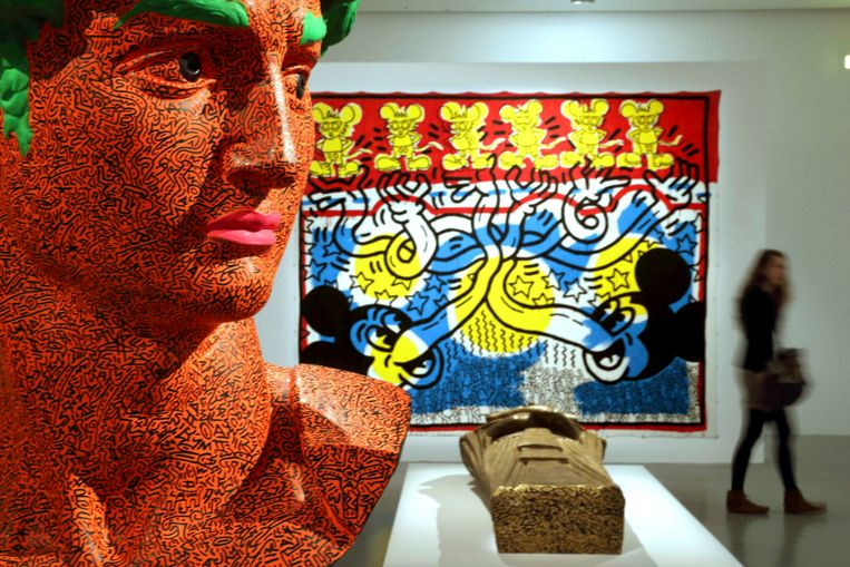 A visitor walks past 'Sarcophagus' (in collaboration with LAII) (C), a sculpture, Untitled, 1984 (L), and a creation, Untiltled, 1985 (Rear) by the late American artist Keith Haring (1958-1990) during his retrospective exhibition at the Musee d'Art Moderne (Modern Art Museum) in Paris April 18, 2013. The exhibition