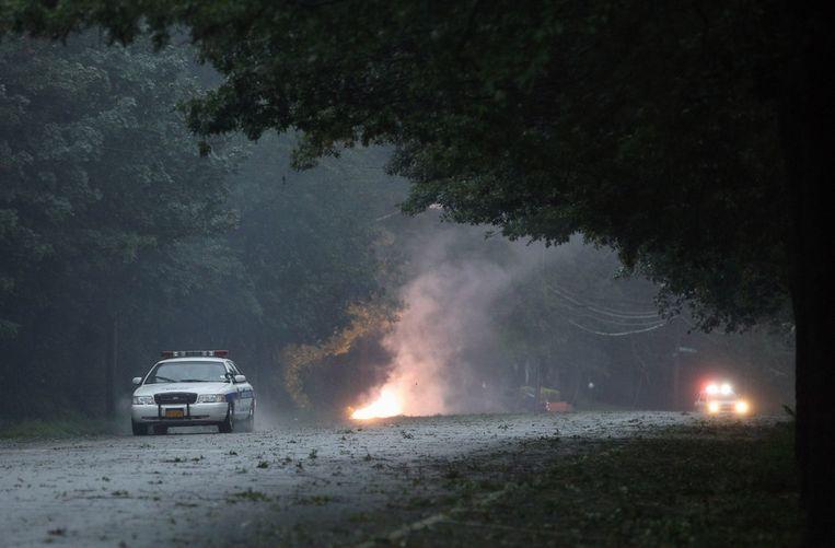 De politie komt kijken naar een brand die is ontstaan door electriciteitskabels die naar beneden komen in Bethpage, New York. Beeld getty
