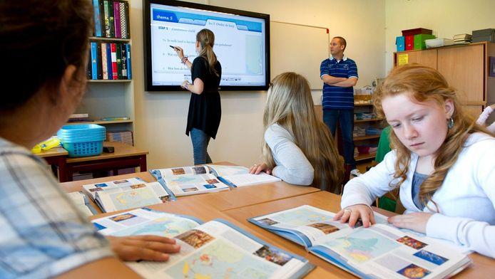 Een leraar geeft uitleg aan de klas op een digitaal schoolbord.