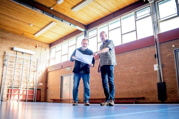Voorzitter Bennie Beernink (links) en beheerder Jos Arntz van De Zandloper bekijken de tekening van de verbouwing, staande in de gymzaal. De muur achter hen bestaat straks uit schuifdeuren, daarachter komt de uitbreiding/opslagruimte.