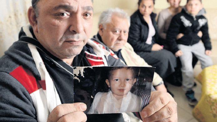 Een familielid van Armandino laat het portret zien van het 3-jarige jongetje dat is ondergebracht bij lesbische pleegouders. 'Een schande is het.'