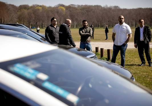 Taxiondernemers verzamelen op het Malieveld om een petitie te overhandigen aan het ministerie van Economische Zaken.