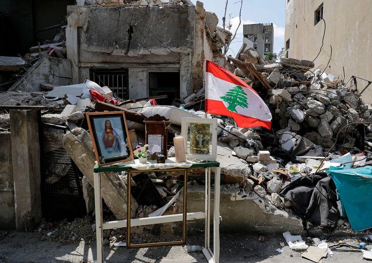 Een eenvoudig altaartje tussen het puin, als eerbetoon aan een overleden inwoner.  Beeld Hollandse Hoogte / AFP