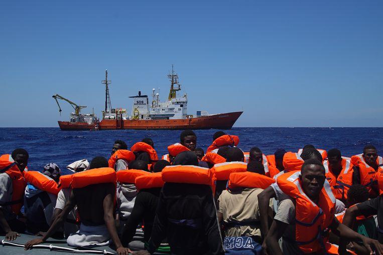 Vluchtelingen hebben van de bemanning van de Aquarius, op de achtergrond, reddingsvesten gekregen. Ze gaan weldra aan boord. Beeld Bram Janssen/AP