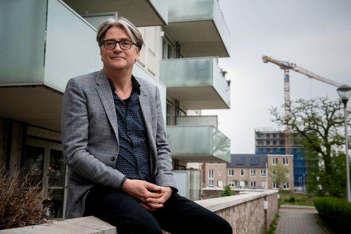 """René Scherpenisse bij de Caspar Houbenflat. Op de achtergrond de woningen en appartementen van Aan de Waterkant. ,,Mensen met allerhande rugzakjes komen dus niet in de Blaak."""""""