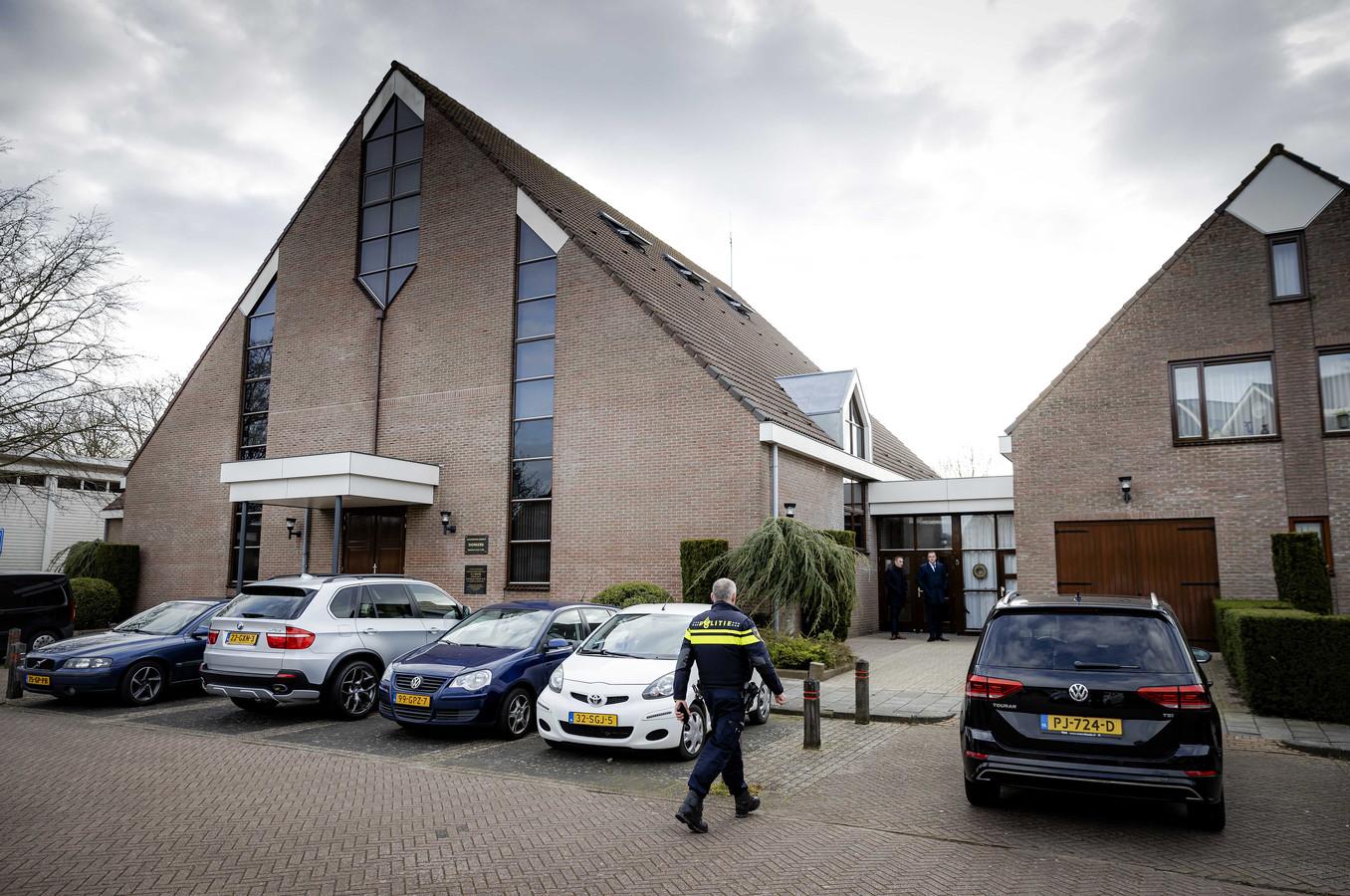 Een politieagent bij de Sionkerk. De Urker Sionkerk heeft besloten de beperkende landelijke coronamaatregelen op te heffen zodat het gebouw weer volledig is opengesteld voor kerkgangers.