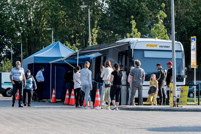 Mensen staan in de rij bij een prikbus van de GGD.