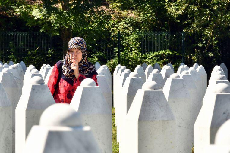 Een Bosnische moslima, overlever van Srebrenica, loopt tussen de graven van haar familieleden op de herdenkingsplaats in Potocari. Beeld AFP