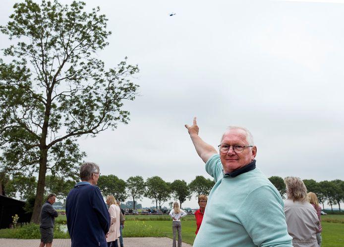 Raadslid Hendrie van Assem wijst de helikopter aan die op 240 meter hoogte boven polder Reijerscop vliegt om aan te geven hoe hoog de windmolens reiken.