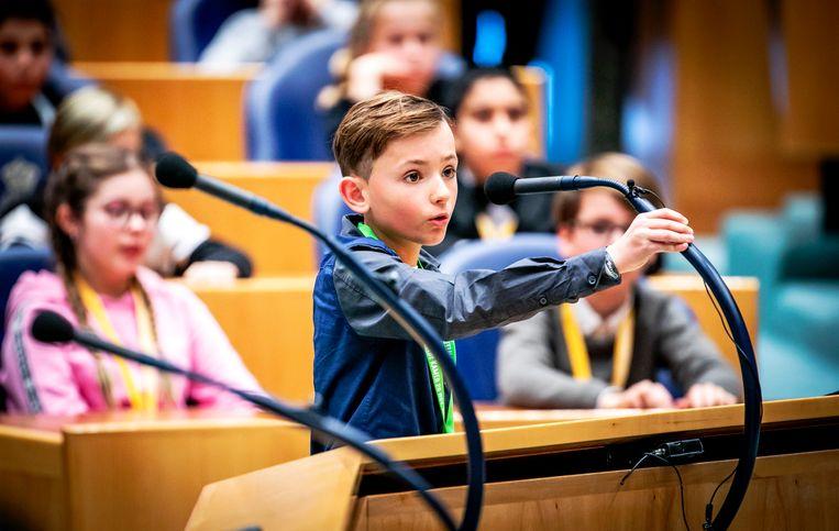 Kinderen uit groep 7 en 8 in de plenaire zaal van de Tweede Kamer tijdens het Kindervragenuurtje op de Internationale Dag van de Rechten van het Kind. Beeld ANP