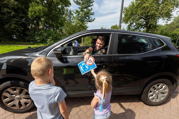 Levi en Chloè, die ook in de Maassluise Verto-wijk wonen, delen stickers uit aan voorbijrijdende automobilisten.