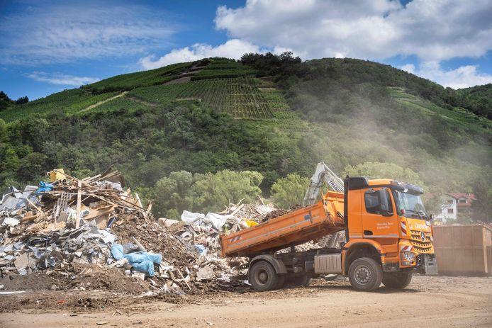 Une photo prise le 30 juillet 2021 montre un camion déchargeant des déchets à la décharge temporaire de déchets dans le village viticole de Rech, près de Dernau, sur la rivière Ahr, dans l'ouest de l'Allemagne, quelques semaines après que de fortes pluies et des inondations ont causé d'importants dégâts dans la région de l'Ahr.