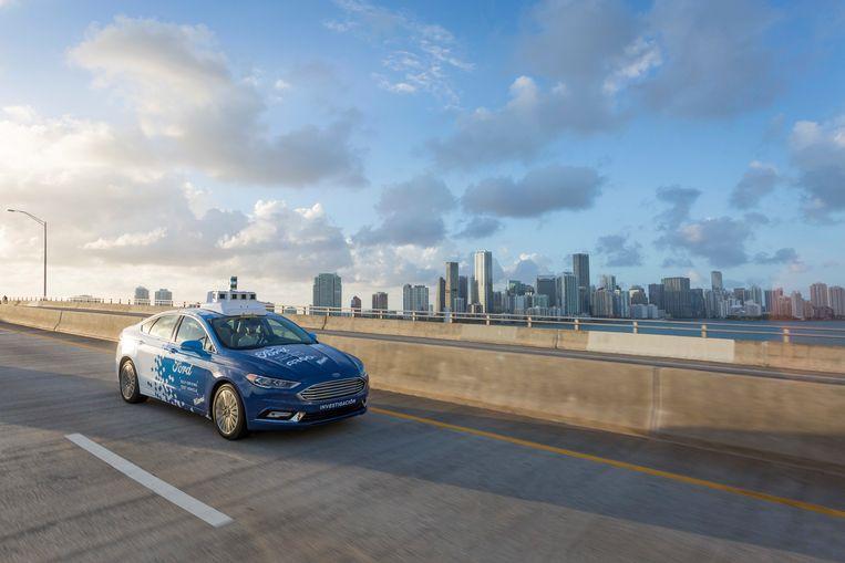 Een zelfrijdende auto van Ford rijdt over de snelweg langs de skyline van Miami.  Beeld AP