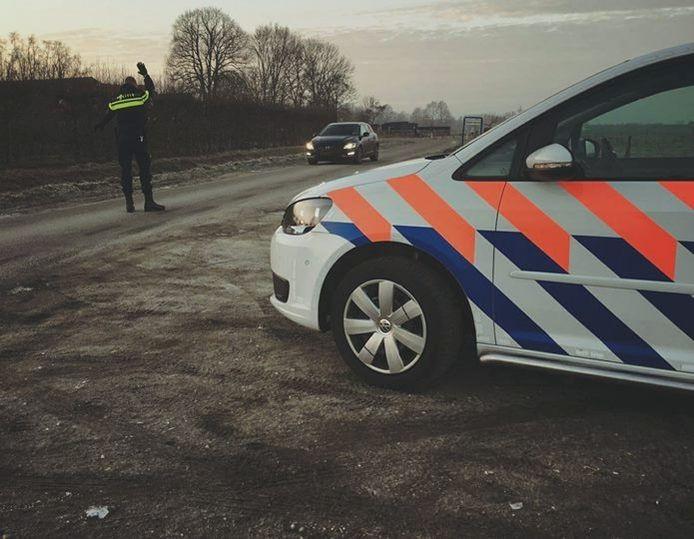 Een agent houdt een automobilist aan op de Abbekindersezandweg.