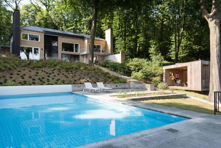 De achterkant van de villa, met haar twee markante schoorstenen. Het poolhouse werd ontworpen door de Brusselse URA-architecten. Beeld Verne