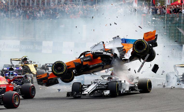 ► De McLaren van Fernando Alonso vliegt in brokken uiteen na de start. Beeld REUTERS