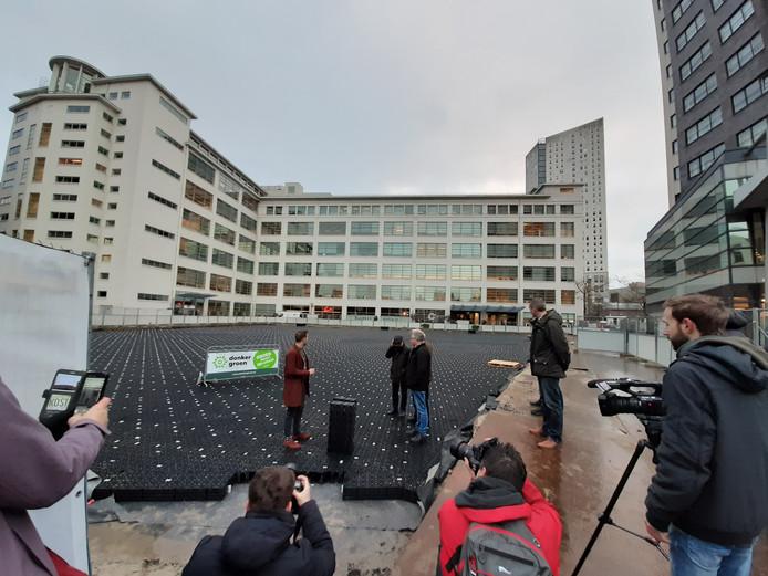Wethouder Rik Thijs (links) legde op het Prins Clausplein in Eindhoven het laatste plastic kratje van de waterberging, samen met enkele buurtbewoners.