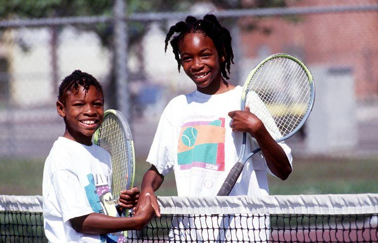 Serena met grote zus Venus op een tennisveld in Compton in 1991.  Beeld Getty Images